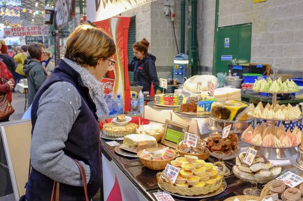 Belfast, Northern Ireland, UK, 10th December 2016. St. George's Market on a Saturday afternoon. A woman looking at cakes on a stall.