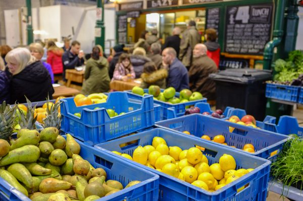 Belfast, Northern Ireland, UK, 10th December 2016. St. George's Market on a Saturday afternoon. Fruit containers with people in the background eating.