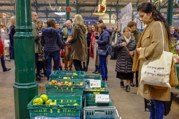 Belfast, Northern Ireland, UK, 10th December 2016. St. George's Market on a Saturday afternoon. A woman examines fruit for sale.